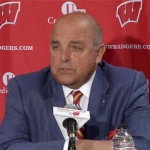 Photo shows University of Wisconsin athletic director, Barry Alvarez, speaking at college football playoff press conference in October 2013.