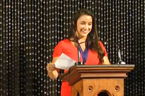 Photo shows Aly Raisman speaking in 2013 at her Hall of Fame induction